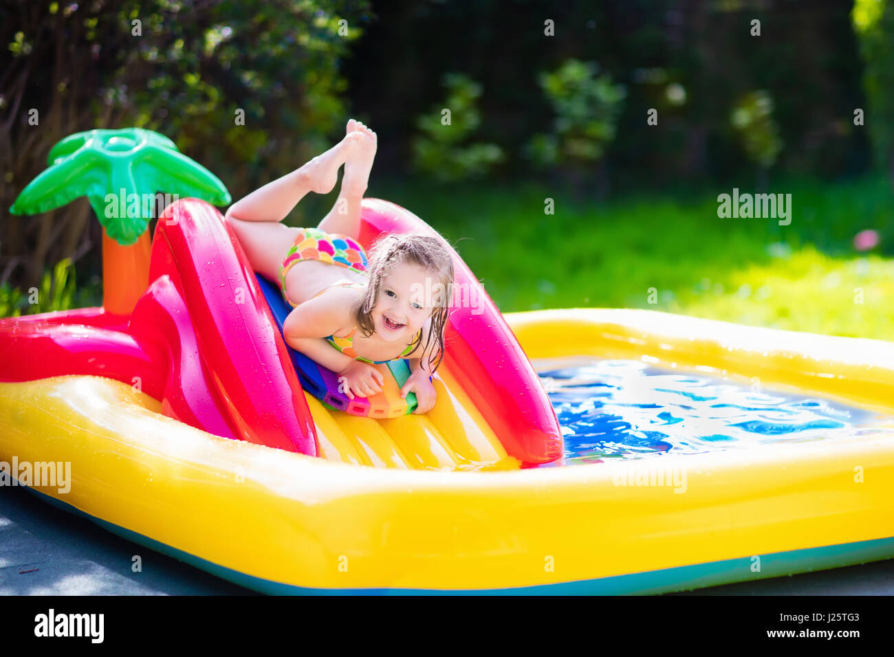 Children playing water hose on stock photos children for Baby garden pool