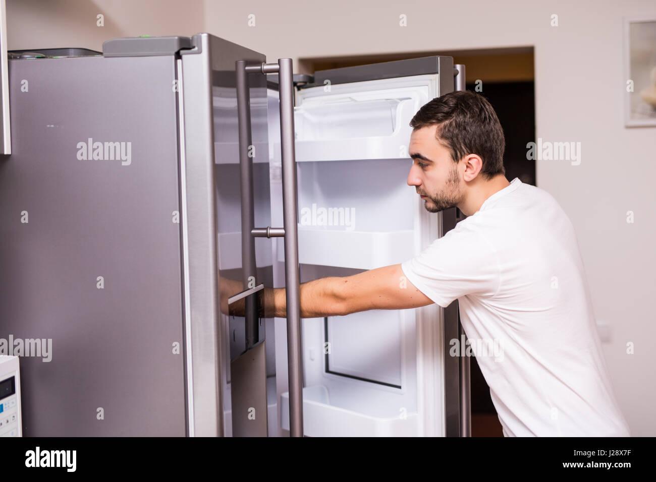 open refrigerator door. man open refrigerator door in the kitchen - stock image a