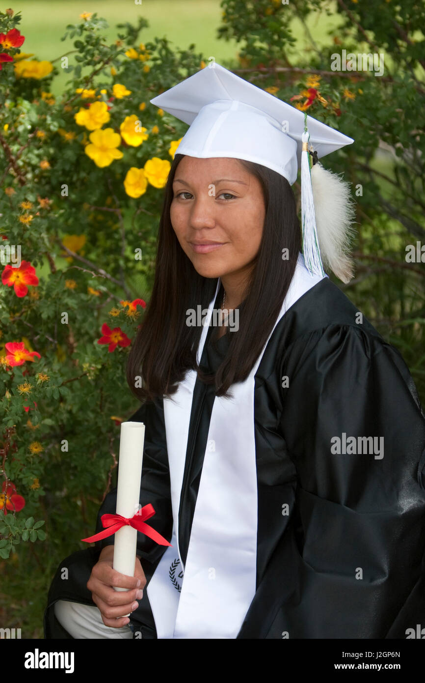 Native American teenage girl dressed in graduation gown and cap ...