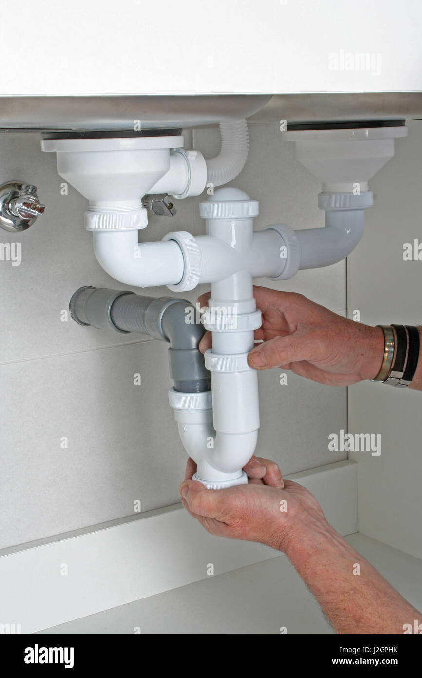 plumber inspecting the drain piping of a clogged kitchen sink J2GPHK