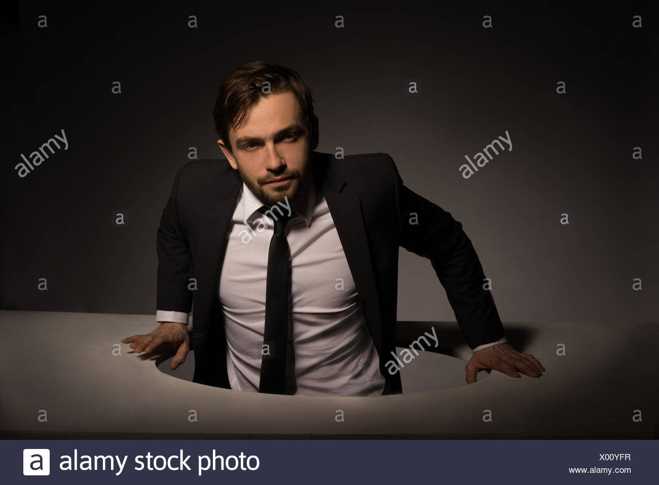 Handsome Young Bearded Businessman Climbing Out Of A Circular Hole In A White Wall In A Conceptual Image