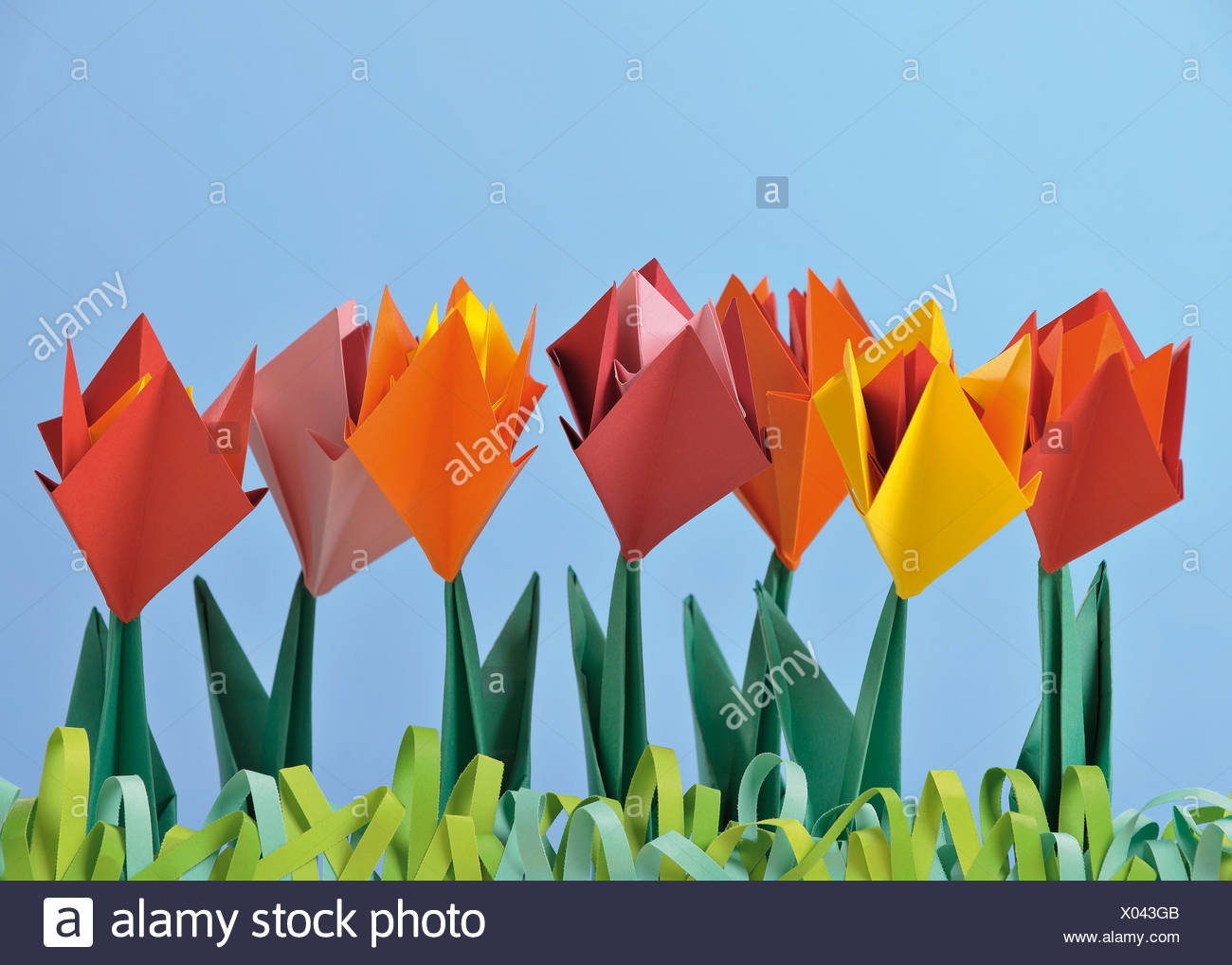 Origami flower tulip stock photos origami flower tulip stock origami tulips against blue background stock image jeuxipadfo Image collections