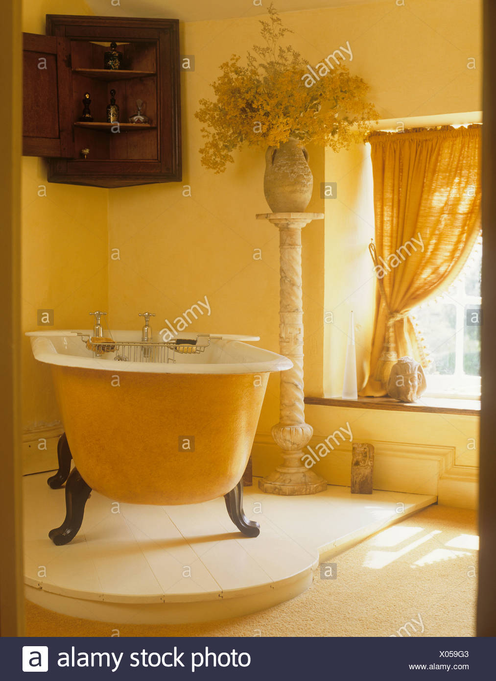 Claw Foot Bath On Raised Floor In Yellow Bathroom With Antique Corner  Cupboard With Vase Of Flowers On Tall Pedestal
