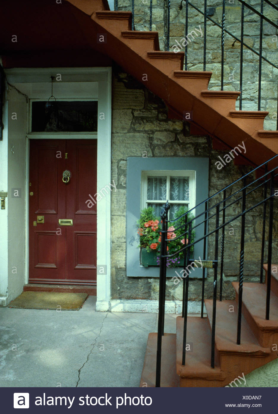 Exterior Of Basement Apartment With A Brown Front Door Below Steps