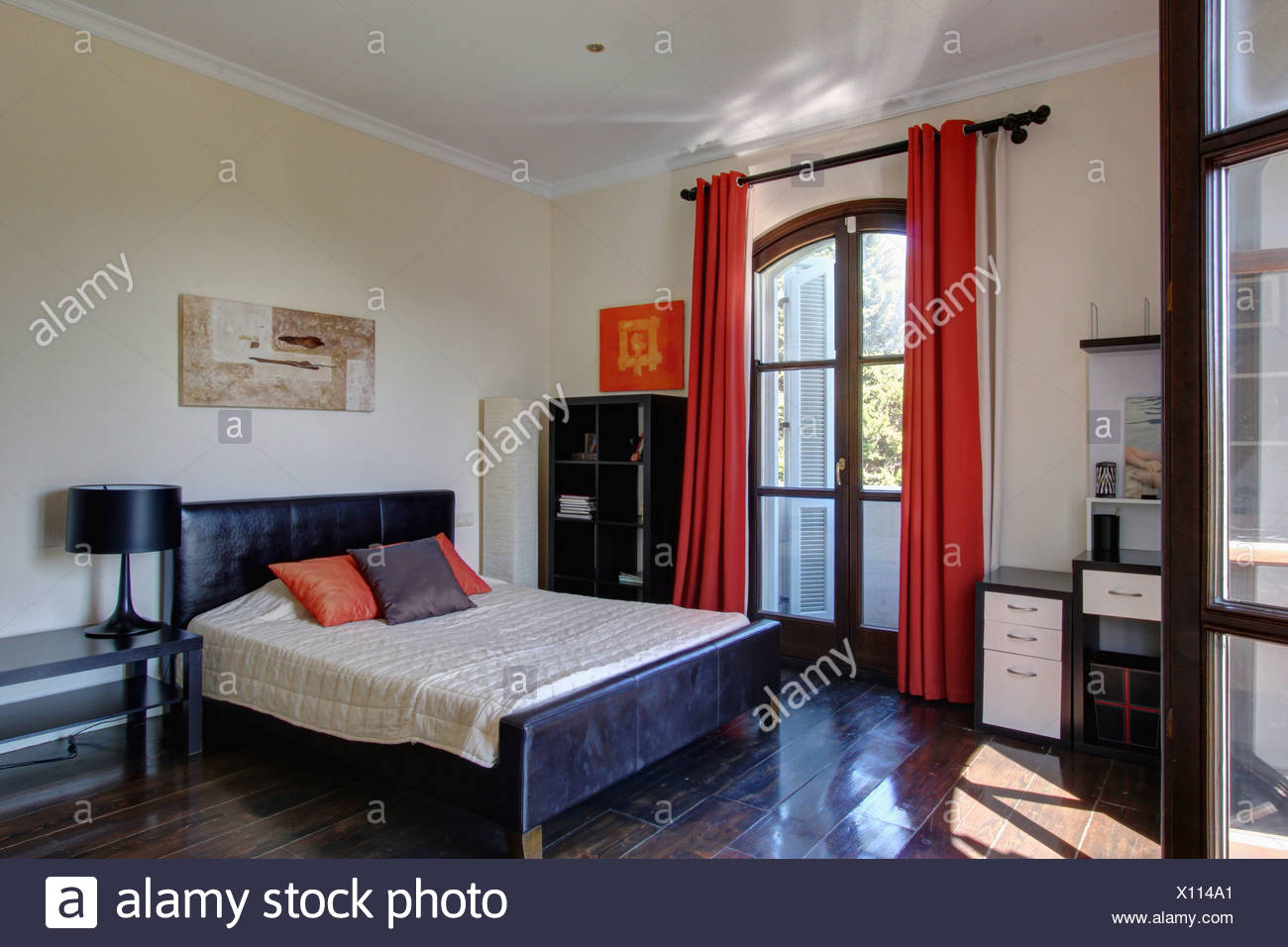Red Curtains On French Windows In Spanish Bedroom With Black Leather  Upholstered Bed And Polished Dark Wood Floor