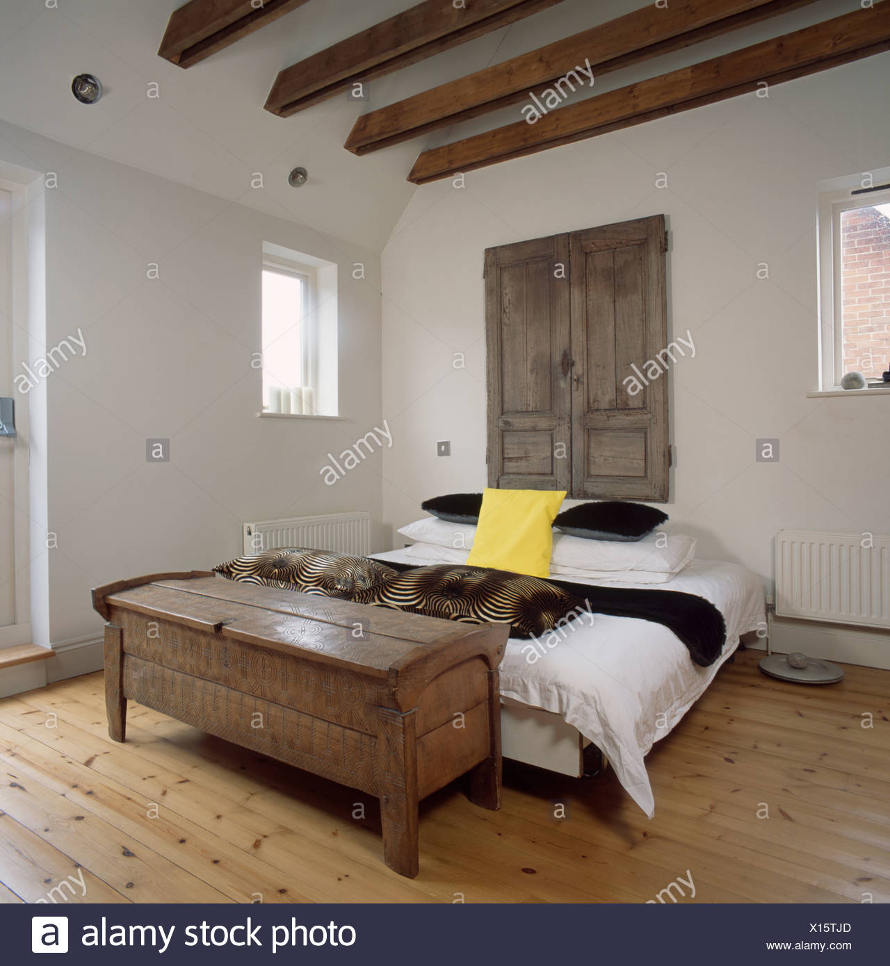 Old Wooden Cupboard Doors Above Bed In Simple White Bedroom With Antique  Wooden Chest And Wooden Flooring