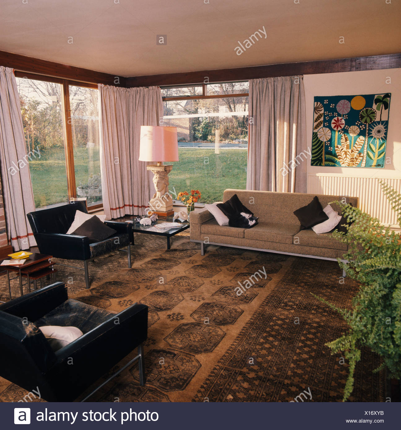 Black Leather Armchairs And Beige Sofa In Sixties Living Room With Brown  Oriental Carpet And White Curtains On Large Windows
