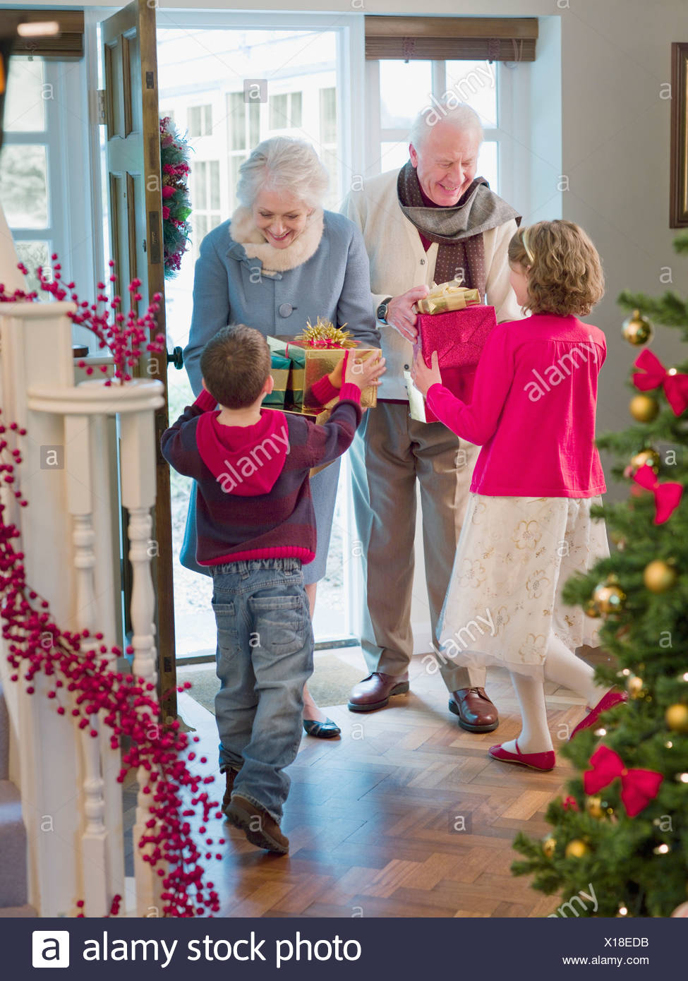 Grandparents giving grandchildren Christmas gifts in doorway Stock ...