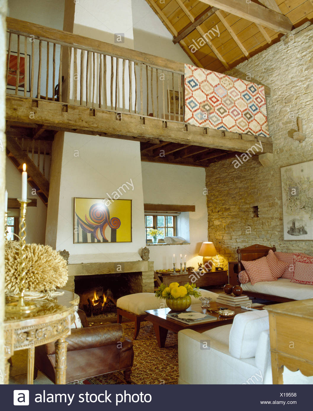 rug draped on rustic banisters on mezzanine gallery above barn