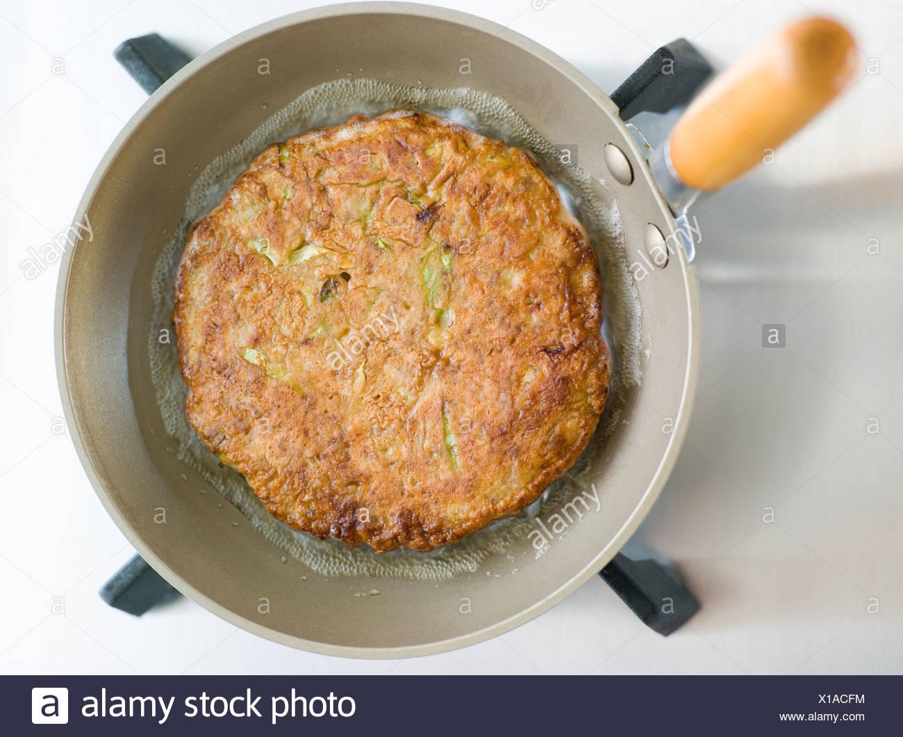 savoury pancake cooking in a japanese frying pan stock photo