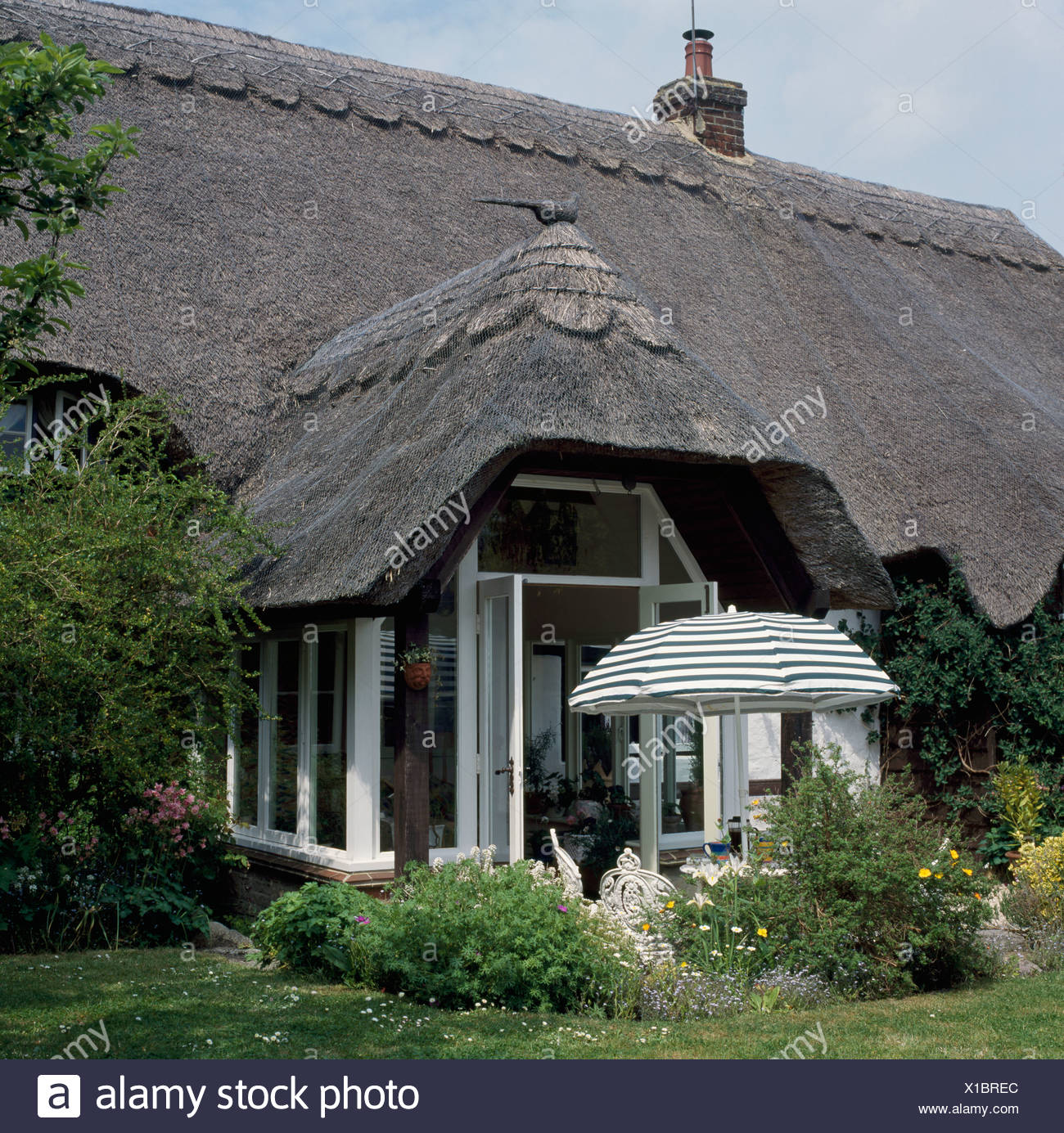 White Thatched Cottage With Thatched Conservatory Extension And Patio With  Striped Umbrella