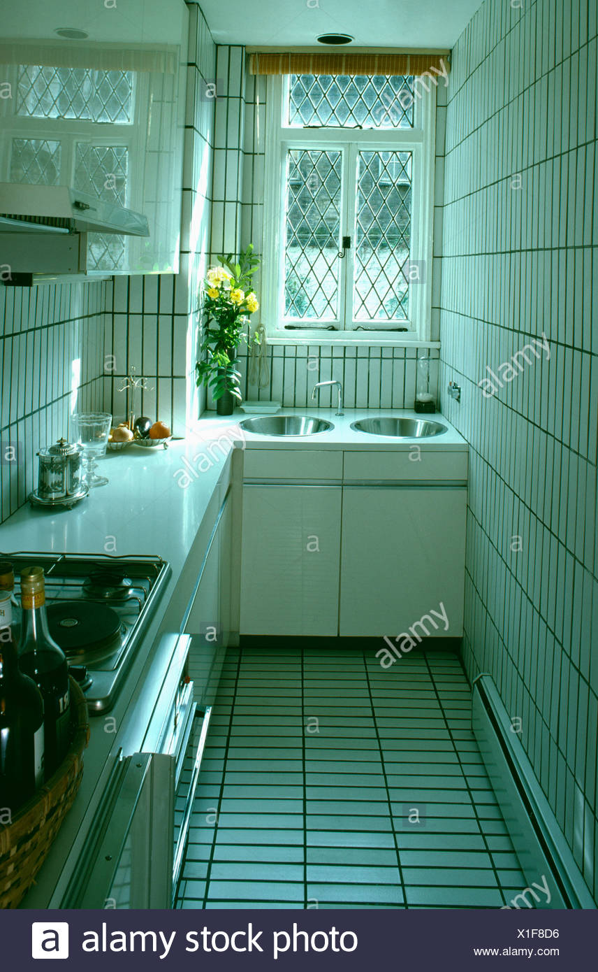 Double sink below window in small white tiled kitchen Stock Photo ...