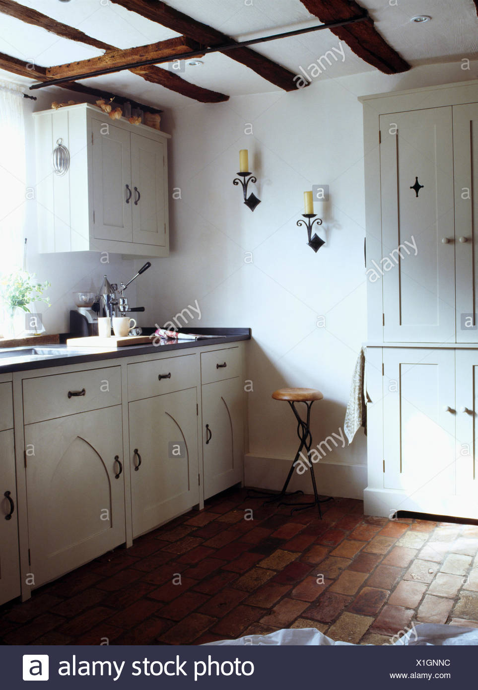 Old brick flooring in white country cottage kitchen