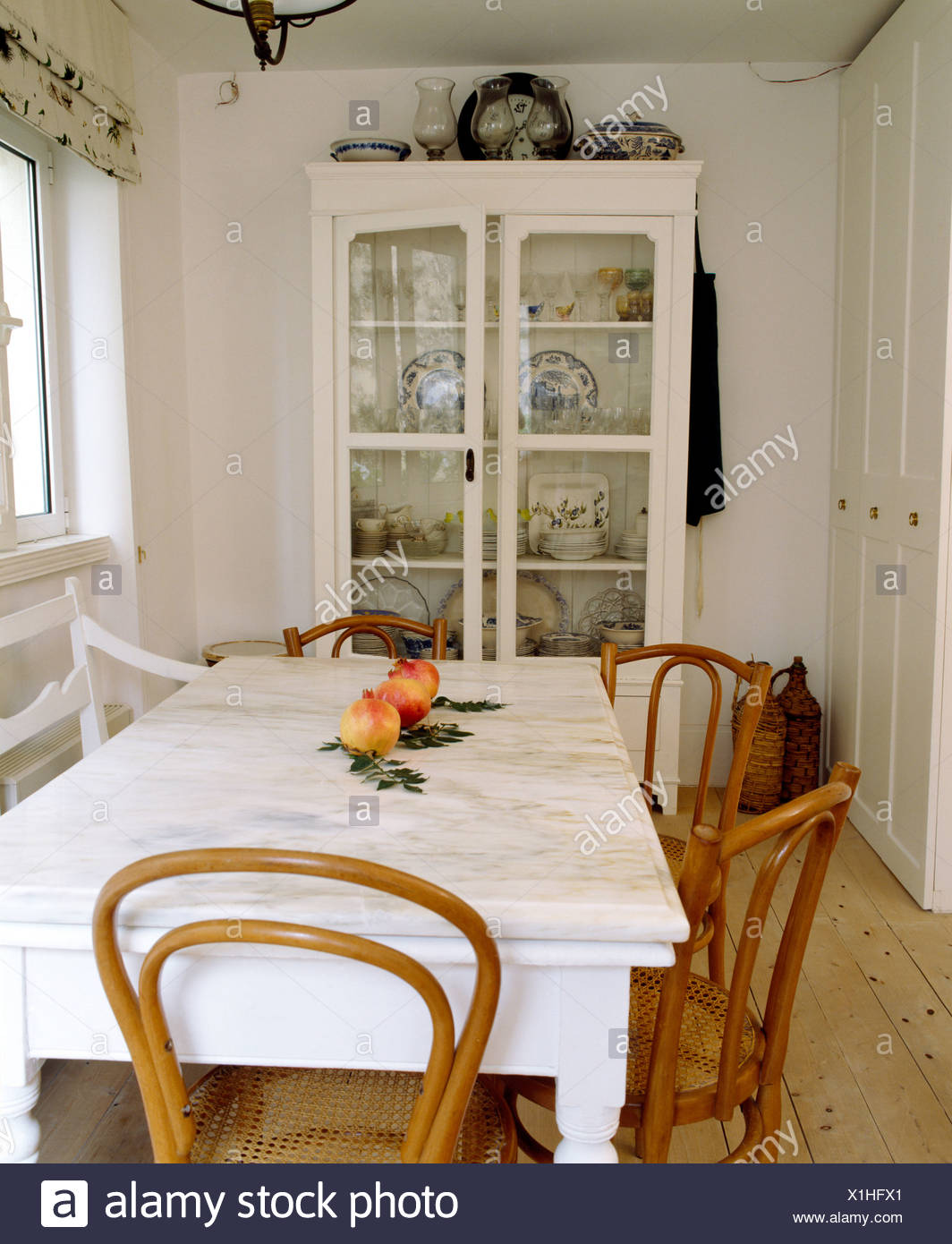 Marble-topped painted table with antique Bentwood chairs in white ...