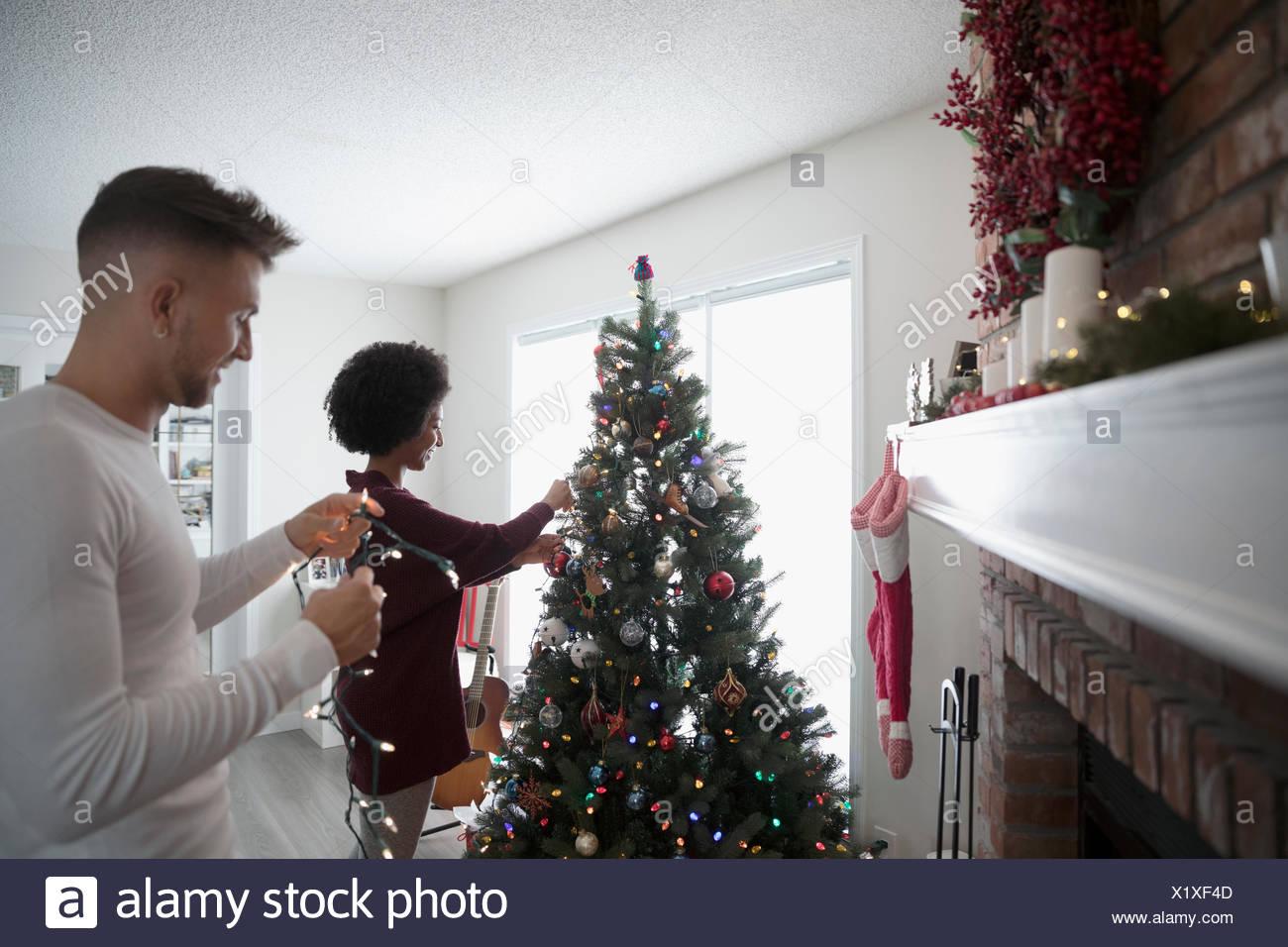 young couple decorating hanging christmas lights on tree in living room - Decorating Living Room With Christmas Lights