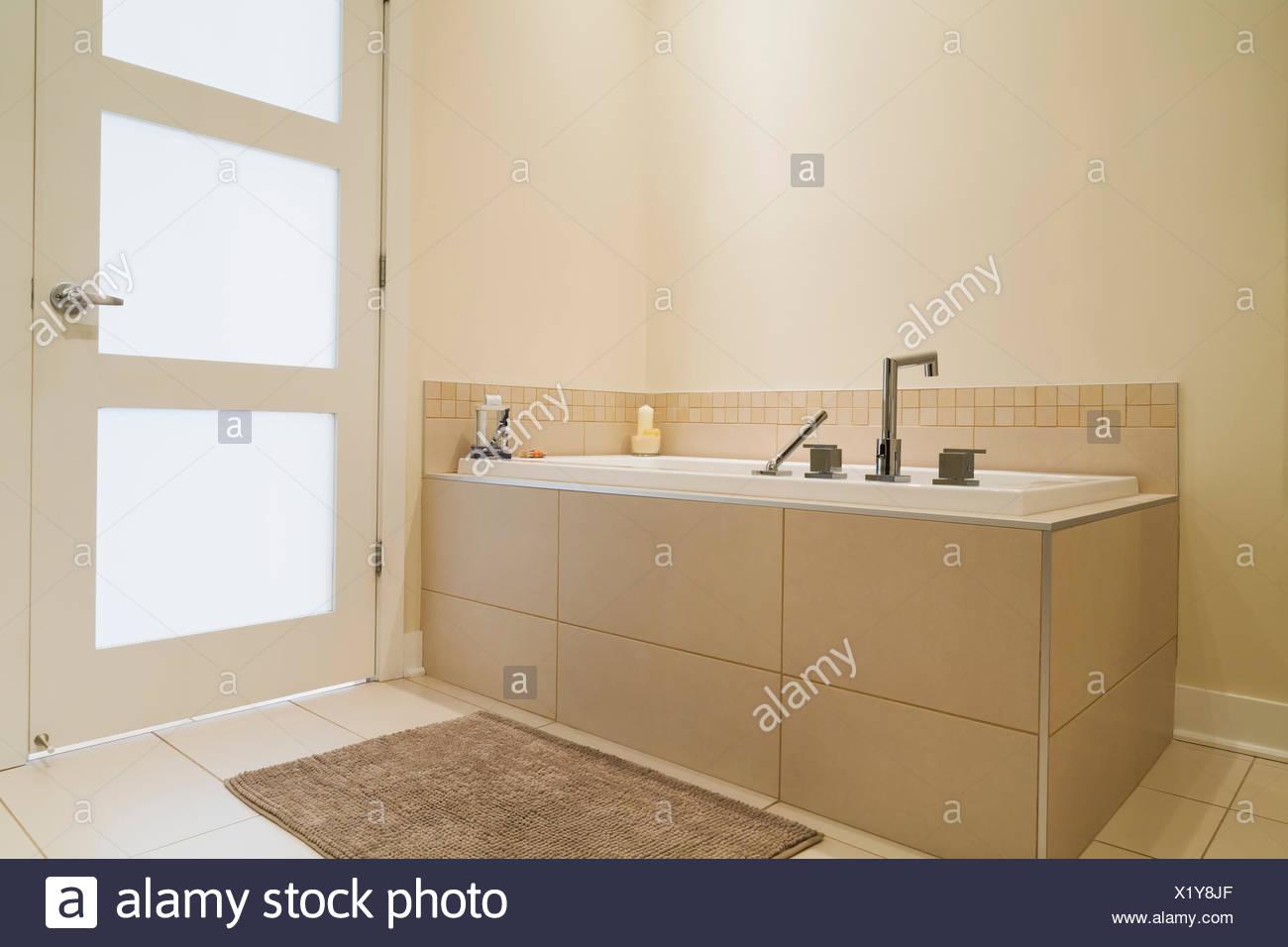 Soaking tub encased in a ceramic tile base in bathroom of renovated ...