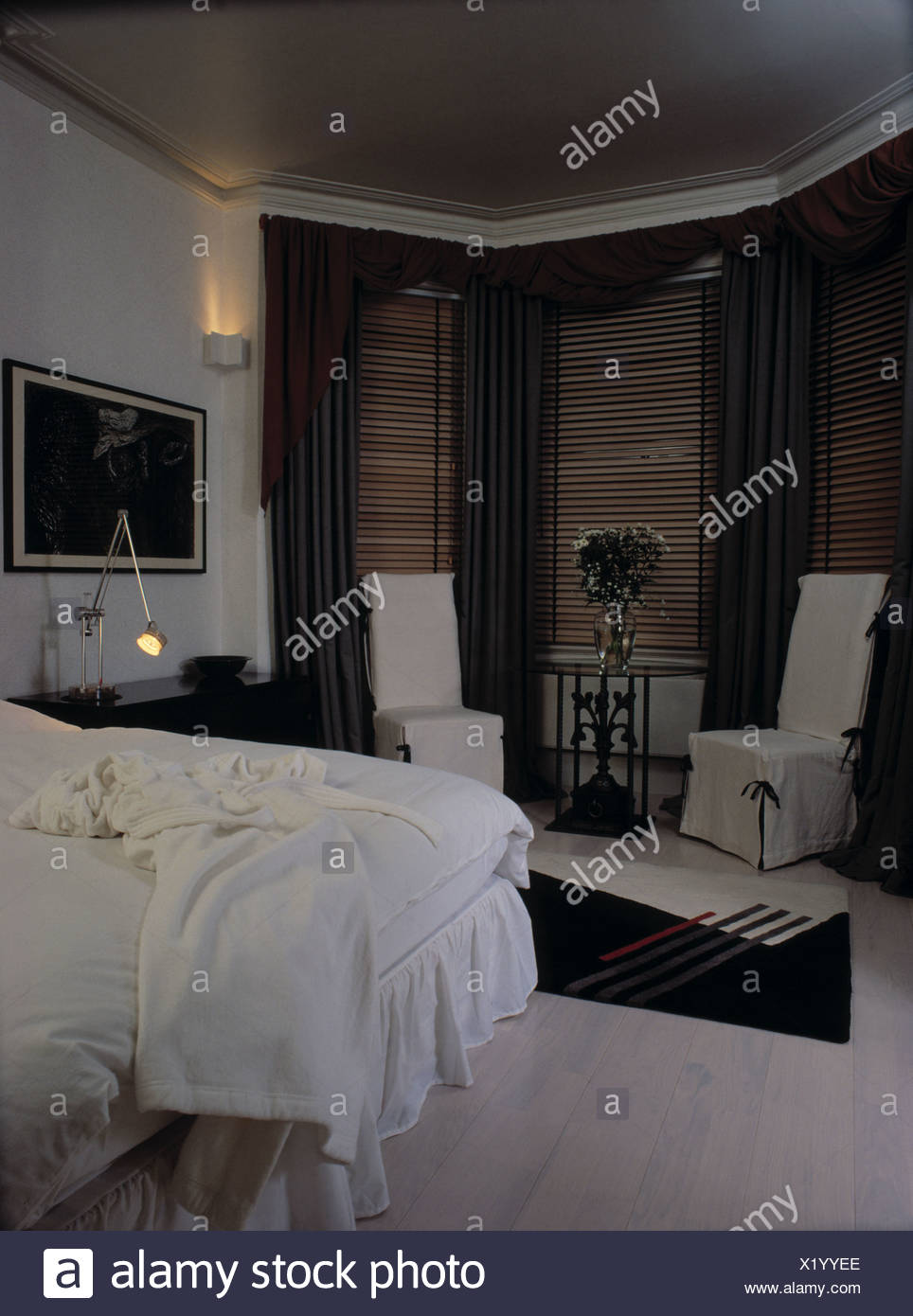 White Loosecovers On Chairs In Front Of Bay Window With Wooden Blinds And Grey  Curtains In White Bedroom With White Bedlinen