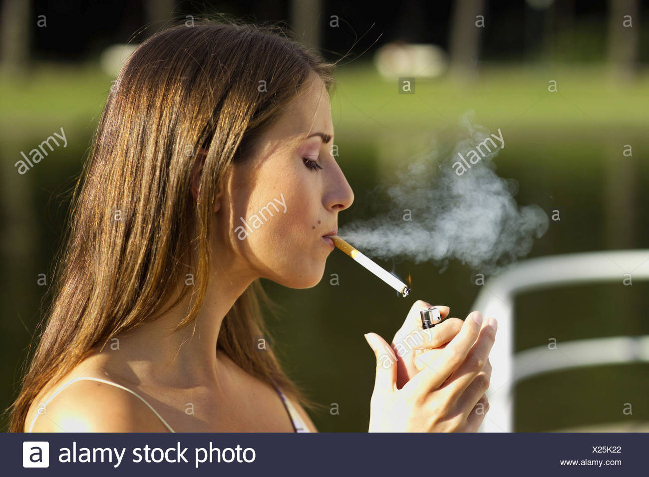 Beautiful Young Woman Lighting Cigarette Stock Photos & Beautiful Young Woman Lighting Cigarette ...