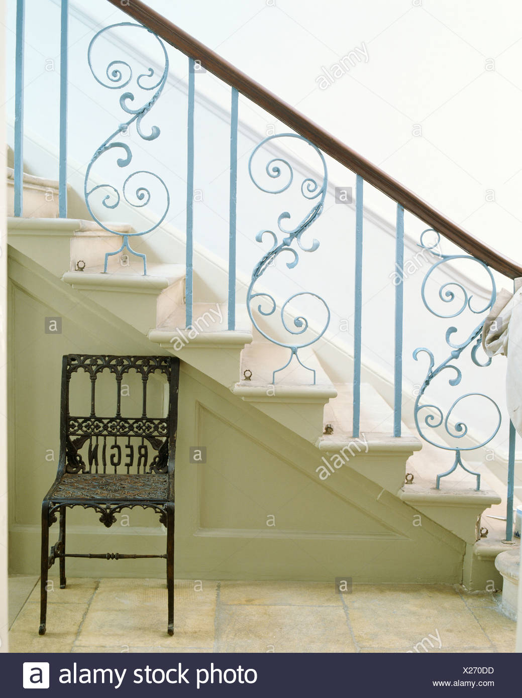 Country Hall With Old Metal Chair Below Stone Staircase With Ornate Metal  Banisters