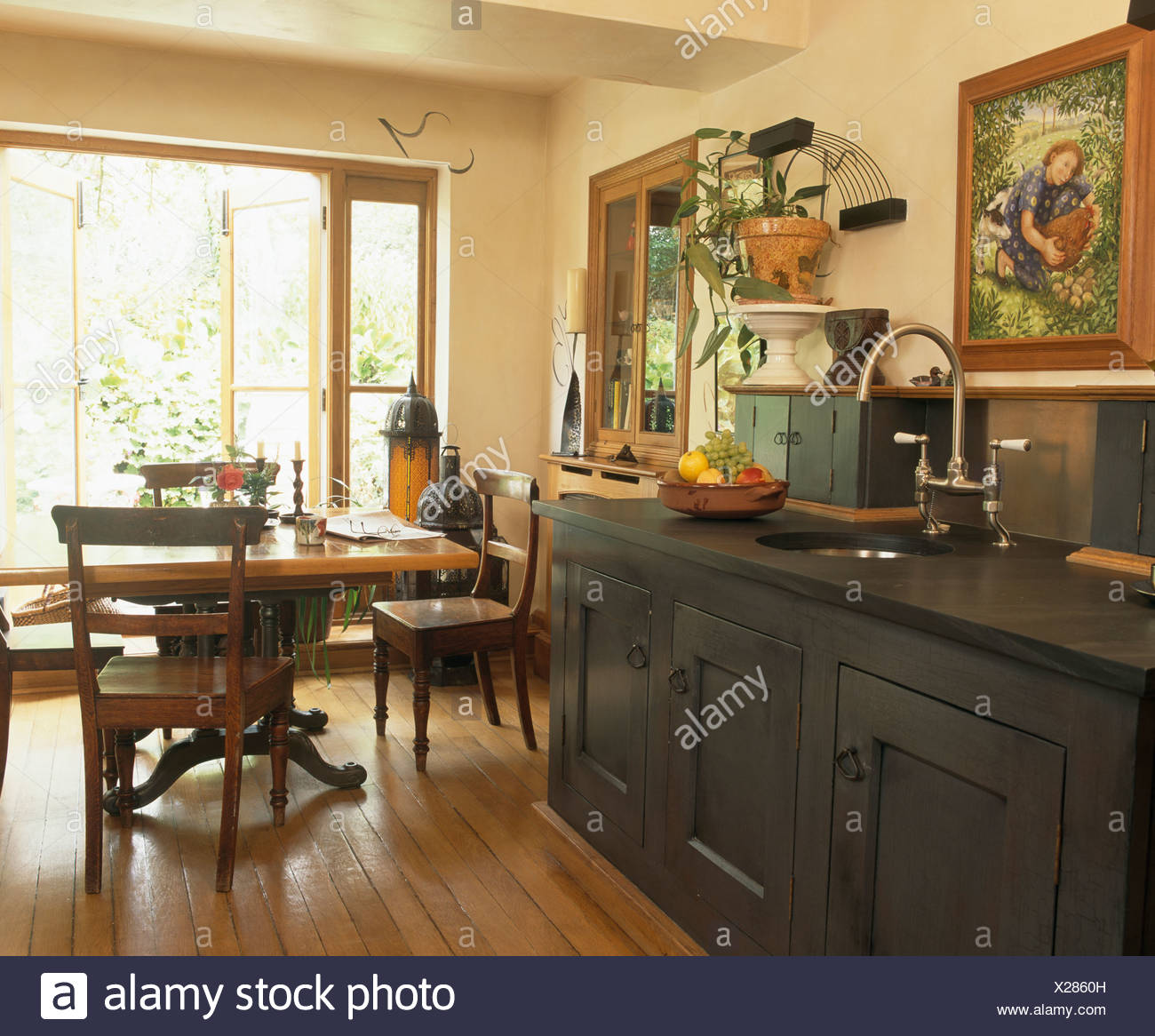 Antique table and chairs in cream country kitchen with reclaimed oak  flooring and dark gray kitchen unit with slate worktop - Antique Table And Chairs In Cream Country Kitchen With Reclaimed Oak