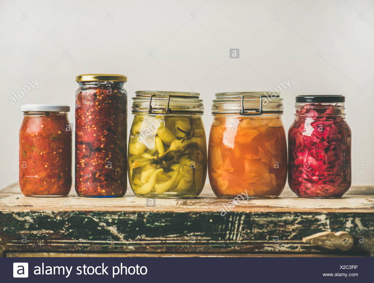 Autumn Seasonal Pickled Or Fermented Colorful Vegetables In Jars Placed In  Row Over Vintage Kitchen Drawer, White Wall Background, Copy Space. Fall Ho