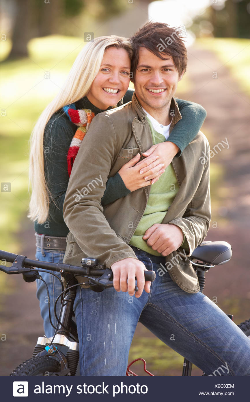 Portrait Of Young Couple With Cycle In Autumn Park Stock Photo