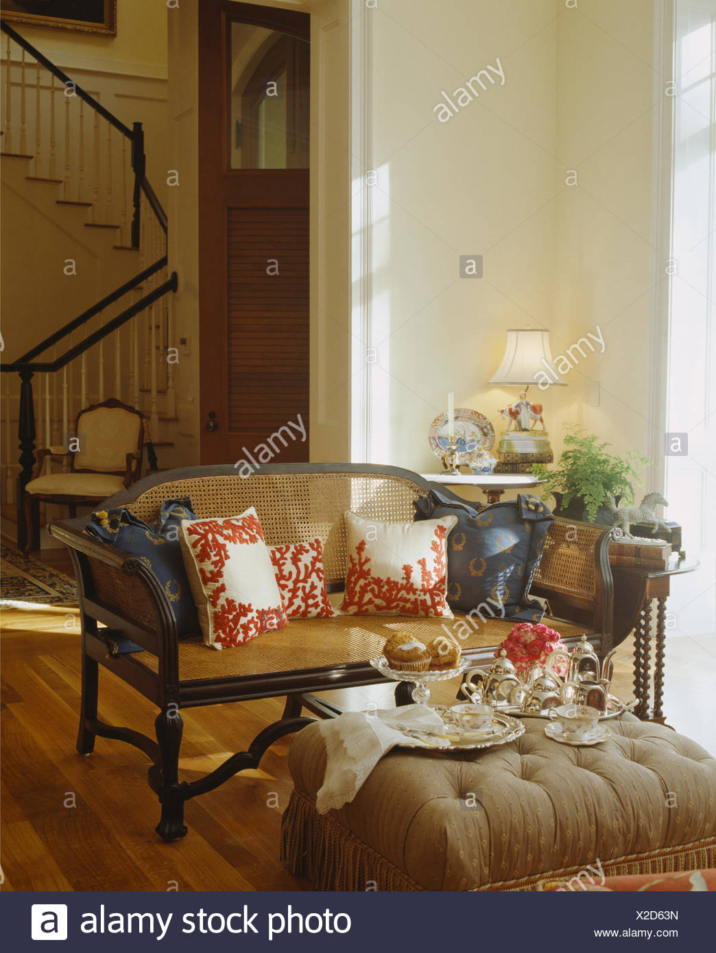 Charmant Tea Set On Upholstered Stool In Front Of Antique Bergere Sofa In Country Living  Room