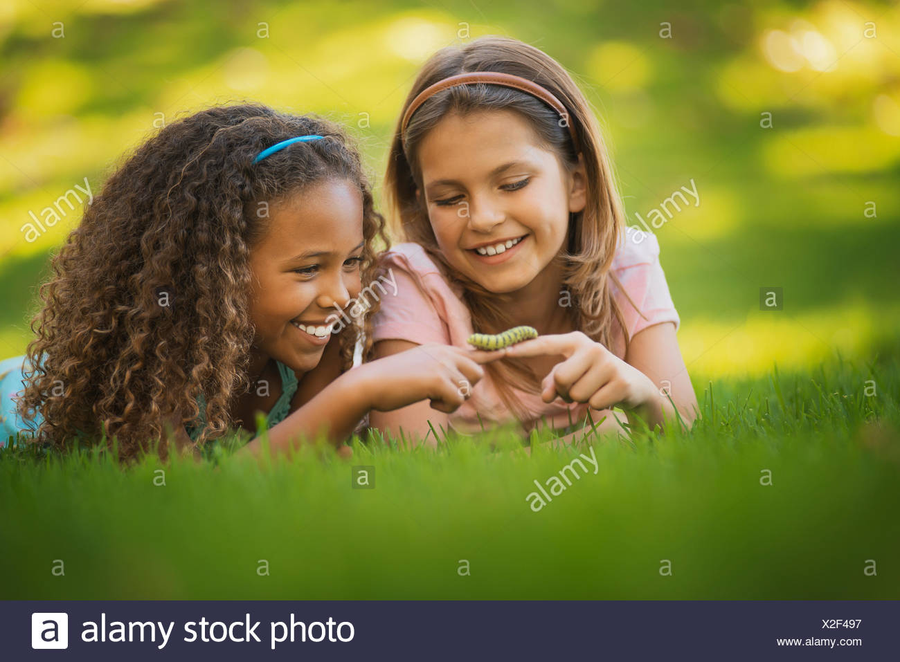 Two Girls Lying On The Grass One Holding A Green Caterpillar Her Finger