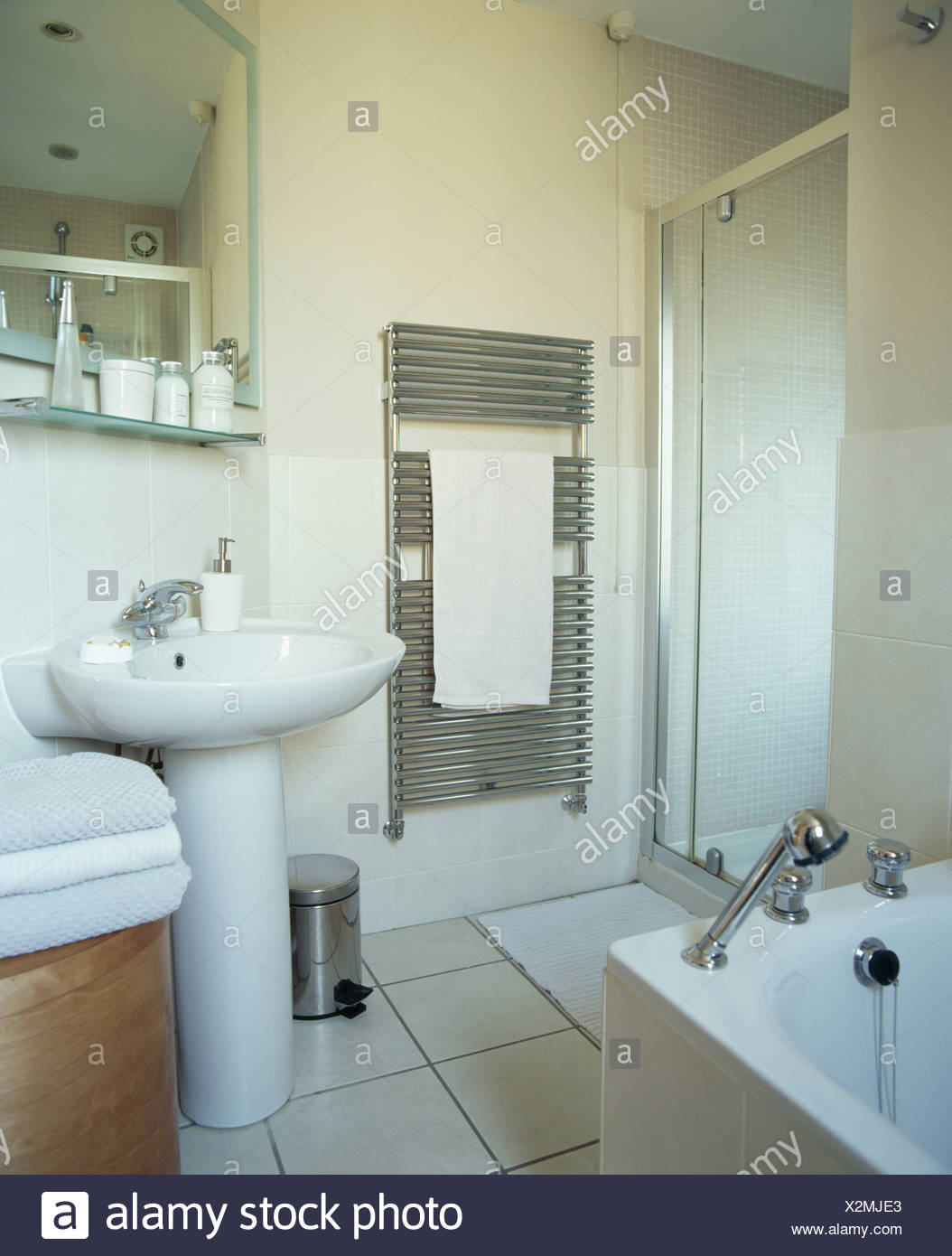 Wall-mounted chrome radiator beside glass shower cabinet and white ...