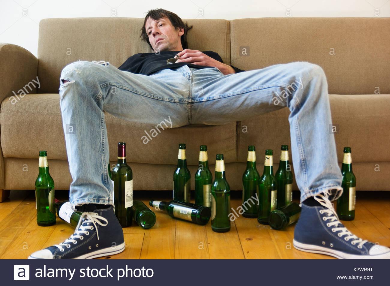 Germany Hessen Frankfurt Drunk Man Lying On Sofa With Empty Beer