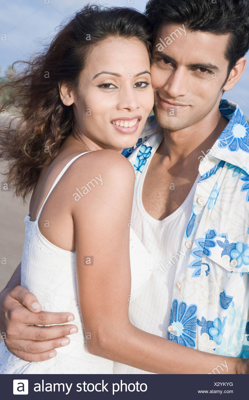 portrait of a young couple romancing on the beach stock photo