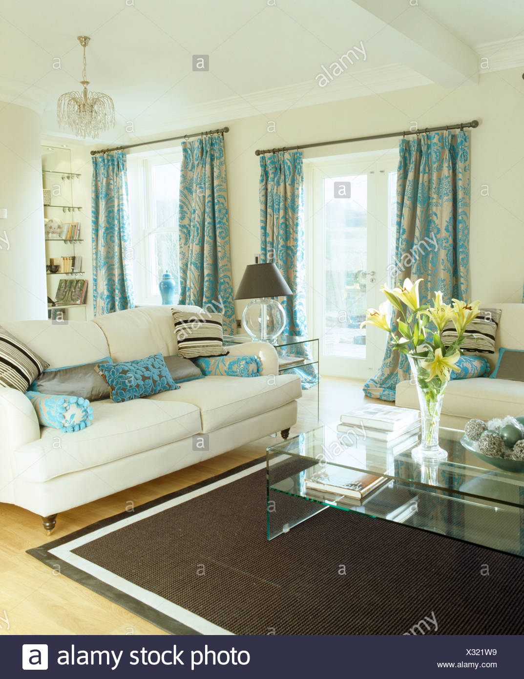 Patterned Turquoise Curtains And Cream Sofas In Cream Living Room With Black  Rug And Modern Glass Table