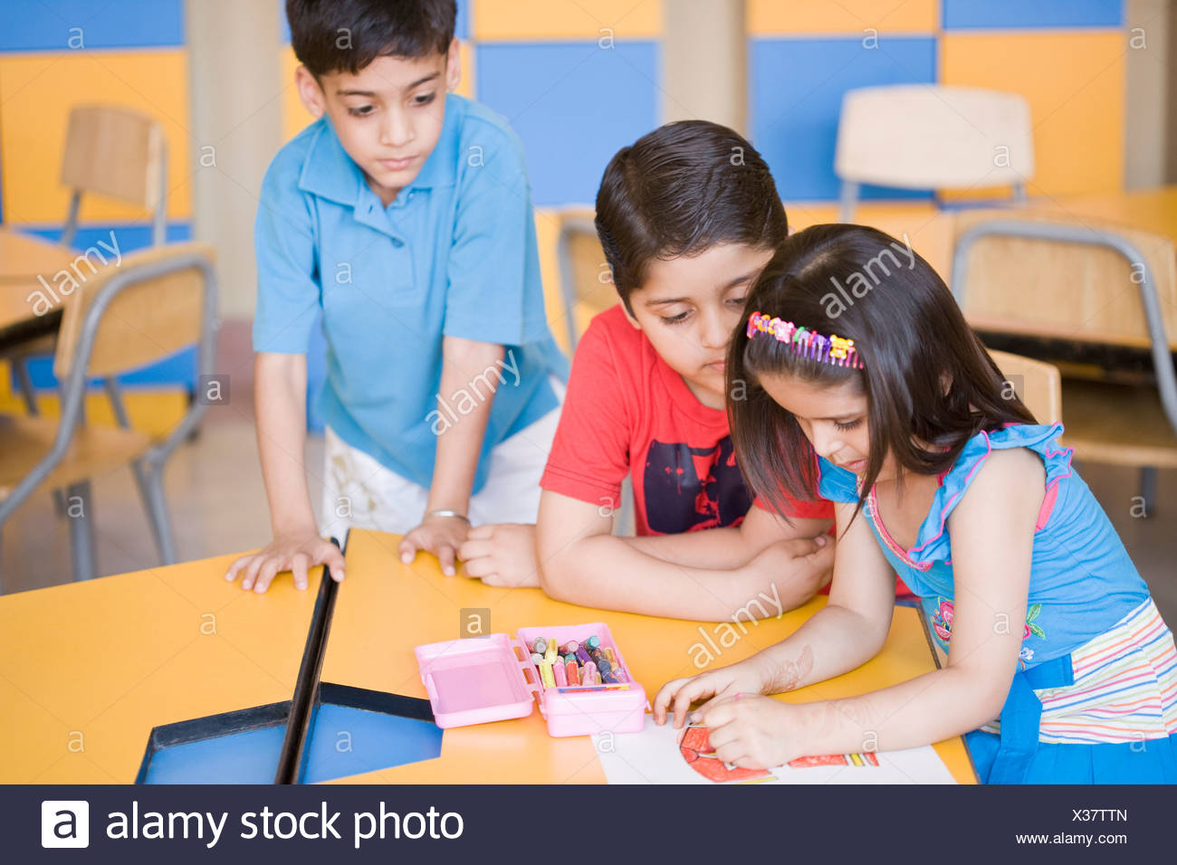 side profile of a girl drawing on a sheet of paper with two boys