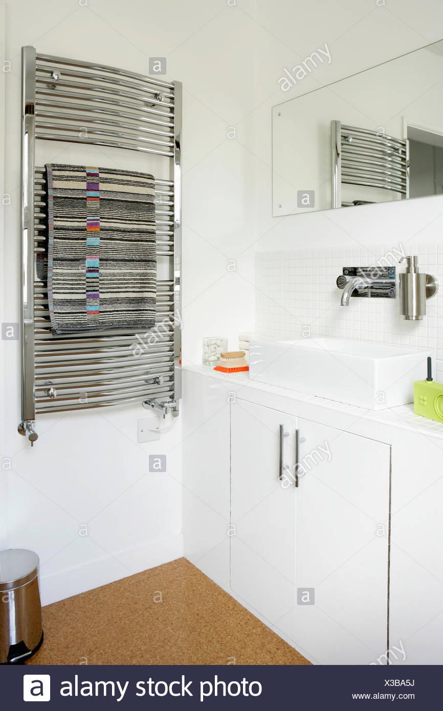 Chrome heated towel rail on wall in modern whtie bathroom with ...