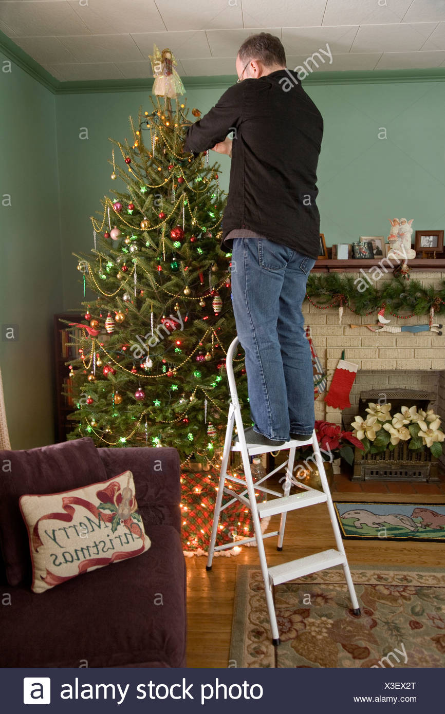 man standing on a ladder decorating the christmas tree whitby ontario - Christmas Ladder Decor