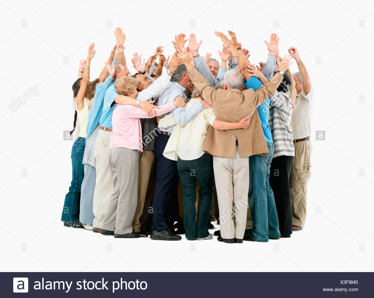 a group of people hugging and raising their arms stock photo