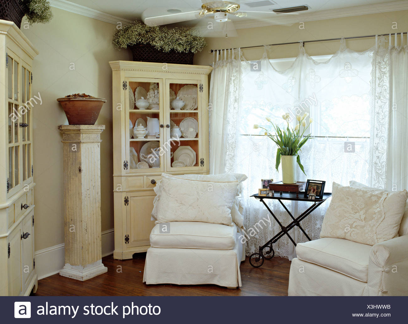 White loose covers on chairs in front of window with lace curtains in cottage living room with painted dresser and tall pedestal