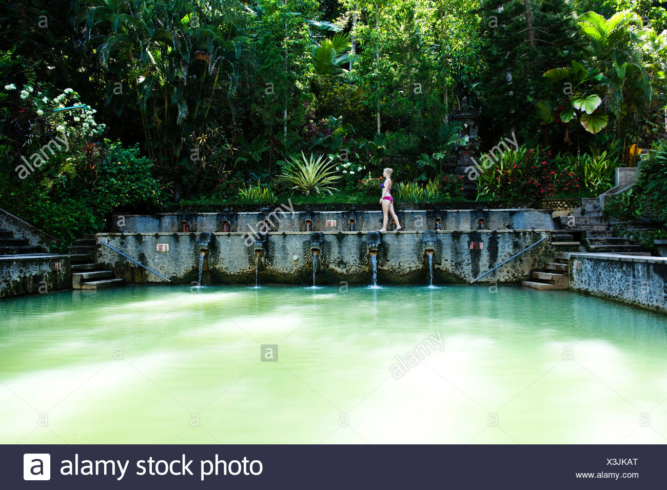 A beautiful woman relaxing next to a hot springs surrounded by a a beautiful woman relaxing next to a hot springs surrounded by a lush jungle and flowers in bali indonesia mightylinksfo