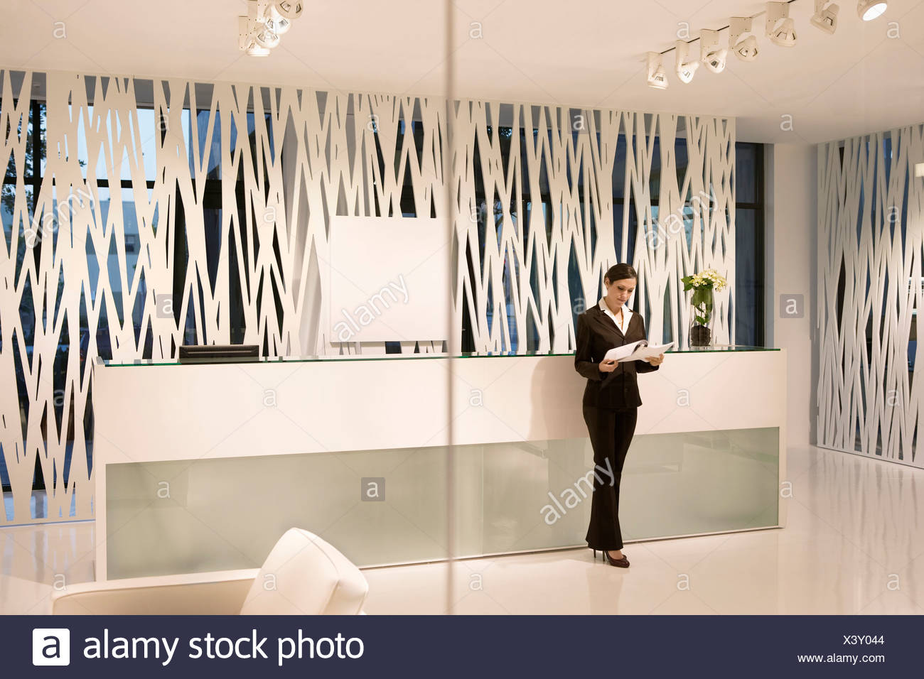 Businesswoman Reviewing Paperwork In Modern Office Lobby