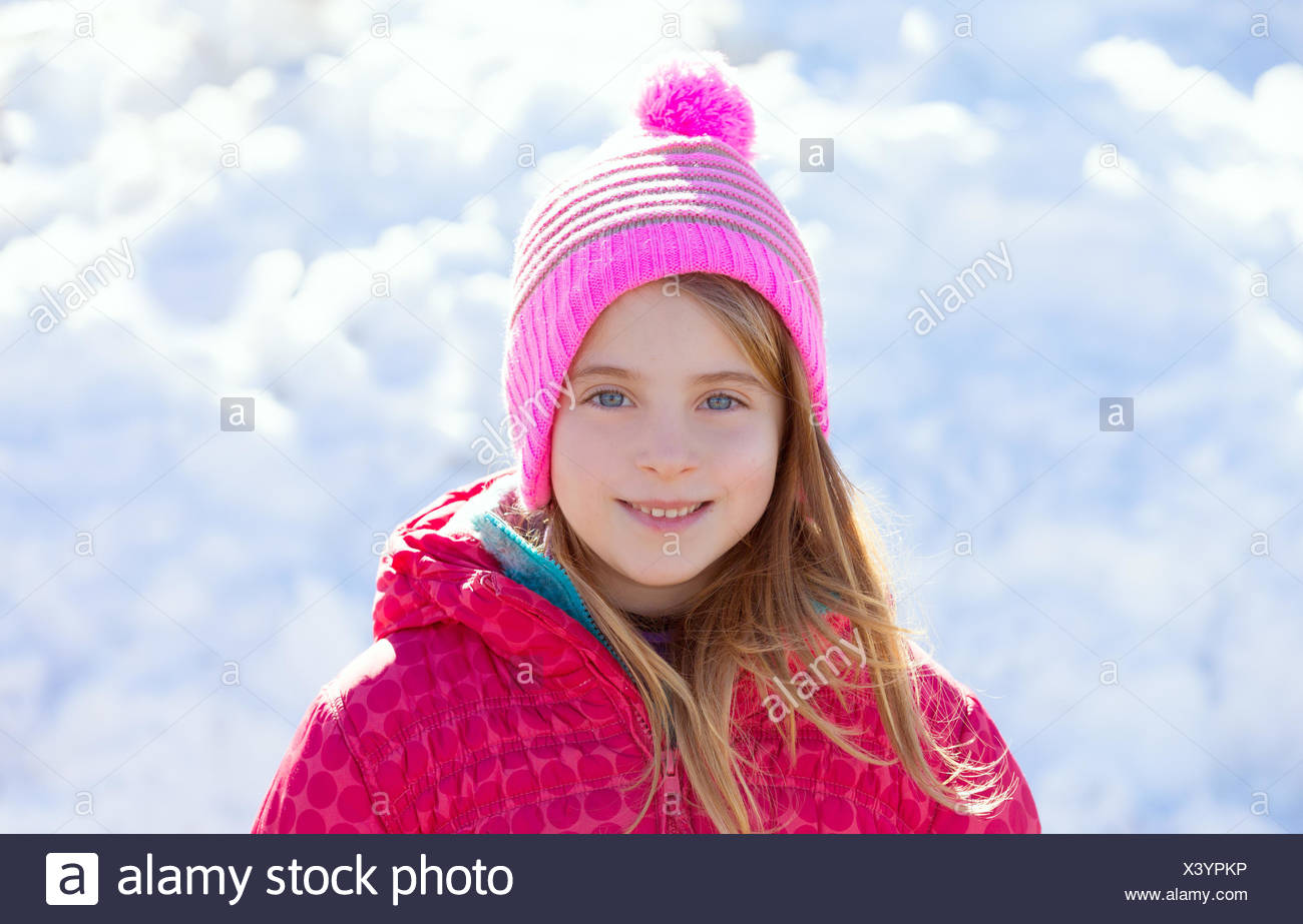 Blond kid girl winter pink hat in the snow smiling happy Stock Photo ... e0df0ed71047
