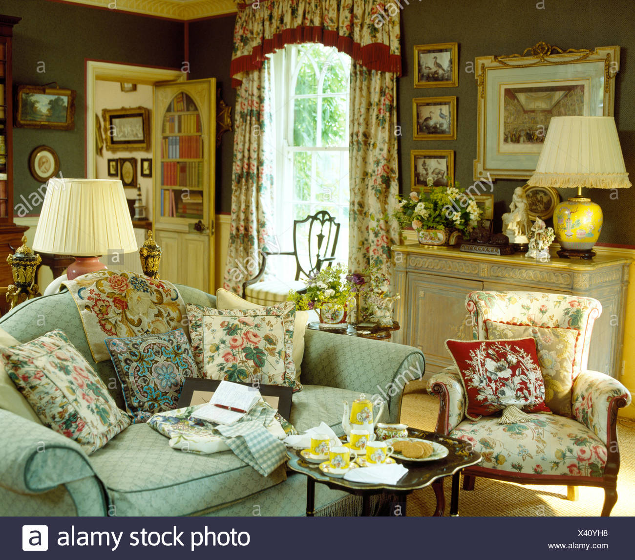 Floral Cushions On Pale Blue Sofa Beside Floral Sofa And Small Table Set  For Tea In Comfortable Green Country Living Room