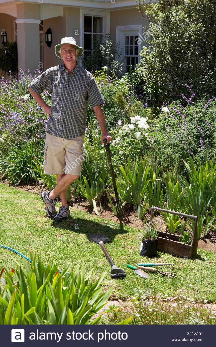 Senior Man Standing On Lawn Gardening Leaning On Garden Fork Hand On Hip  Smiling Portrait