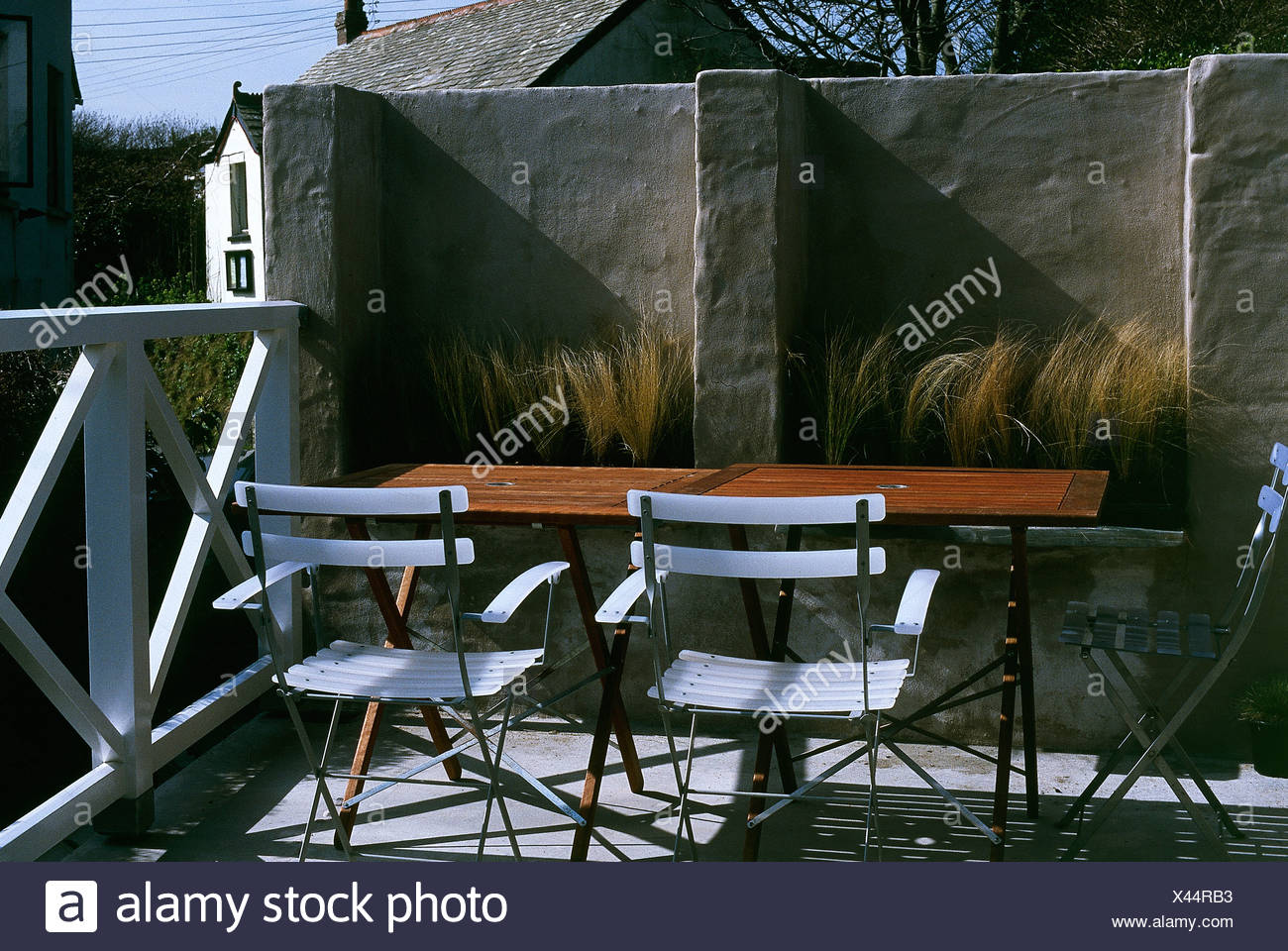 White chairs and simple wood table on raised patio with grasses ...
