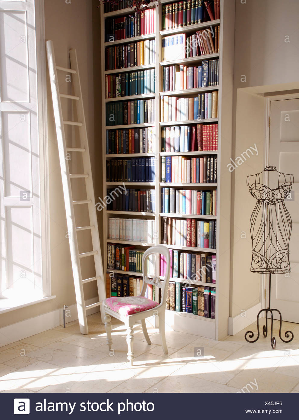 White ladder beside floor to ceiling bookshelves in hall with dressmakers dummy and white painted chair with upholstered seat