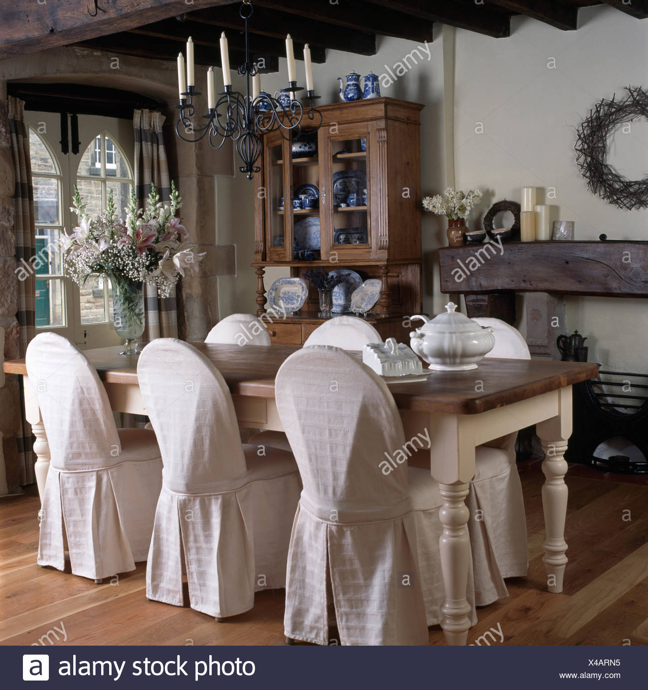 Candle Chandelier Above Painted Dining Table And Chairs With White Textured  Loose Covers In A Cottage Dining Room