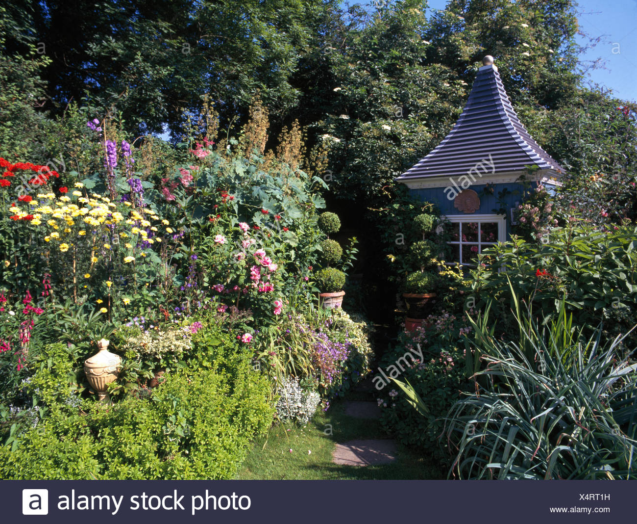 Colorful Perennials In Border Of Country Garden With Elegant Gazebo