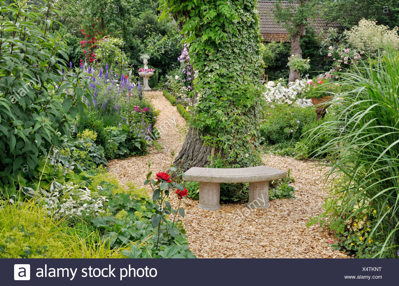 SMALL STONE BENCH IN A PERENNIAL GARDEN. DESIGN: MARIANNE AND DETLEF LUEDKE