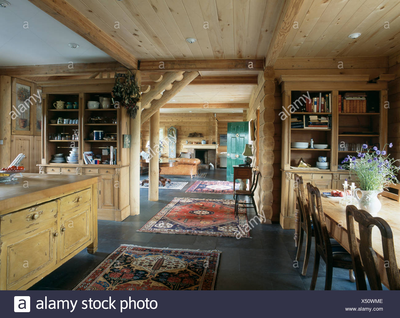Oriental Rugs On Slate Floor In Open Plan Dining Room With Wooden Ceiling  And Log Paneled Walls And Doorway To Living Room