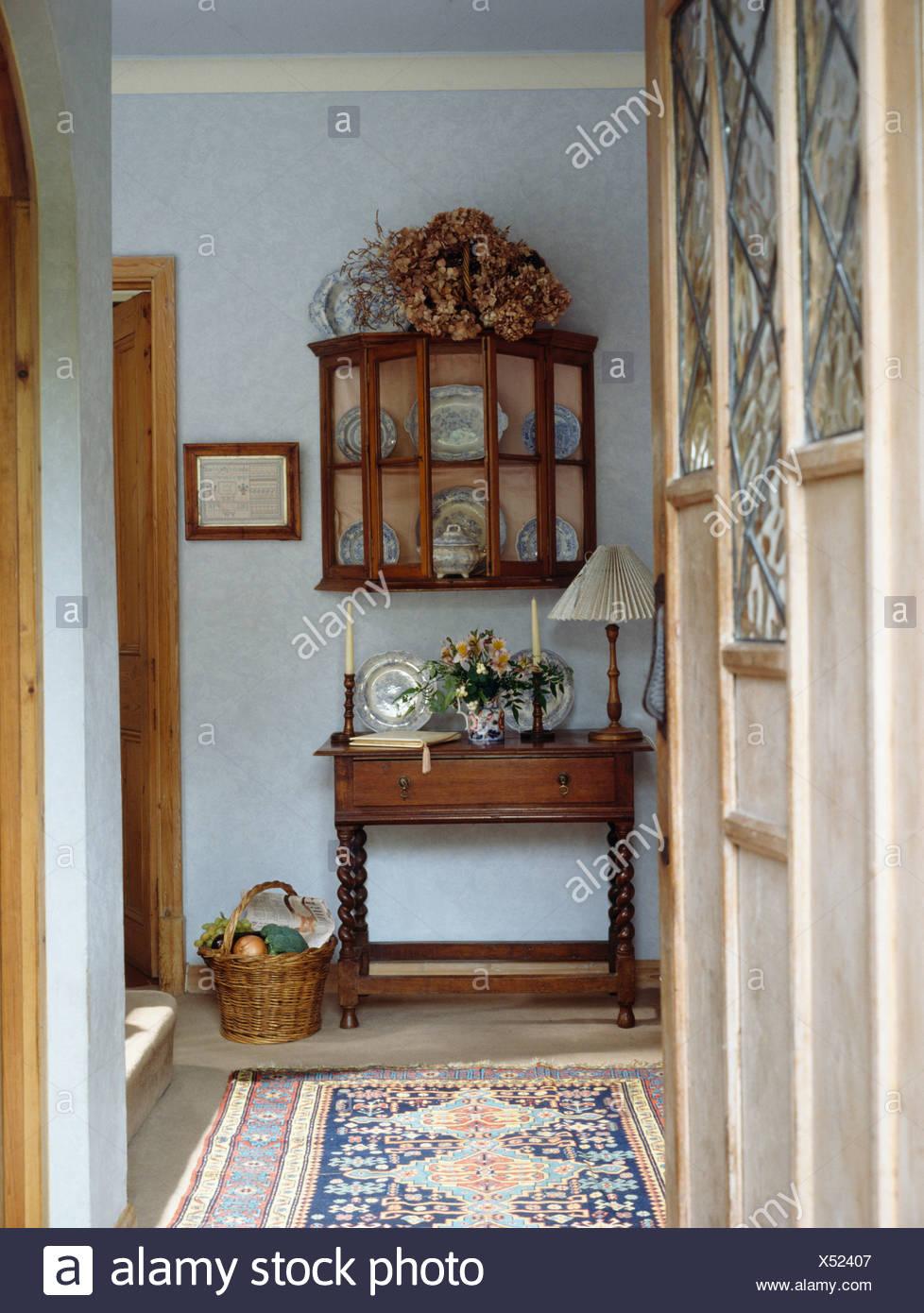 Door open to antique cupboard with glazed doors above table in small blue  hall - Door Open To Antique Cupboard With Glazed Doors Above Table In Small
