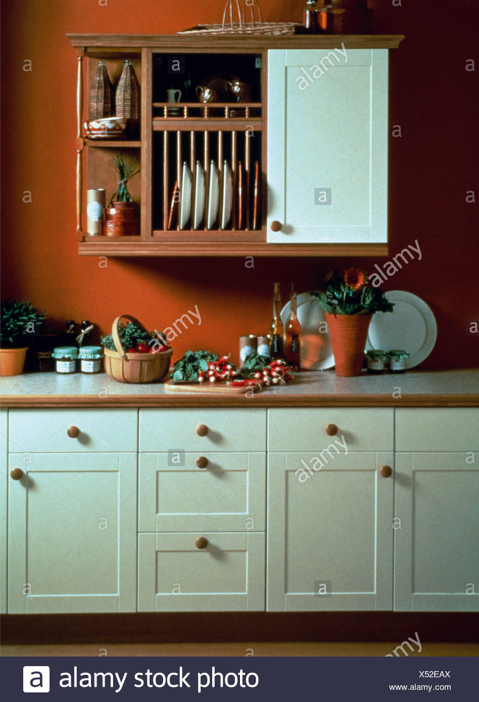 Plate Rack And Wooden Shelves On Wall Unit In Red Kitchen With White Fitted  Cupboards
